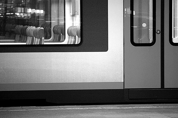 Zwart wit foto van trein op een station.