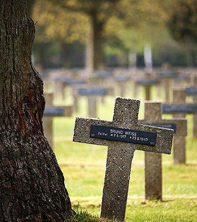 Een Duits Kruis op de Militaire Begraafplaats in Lommel, is schuin gaan staan door boomwortels.