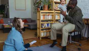 multiracial family having fun with baby in living room