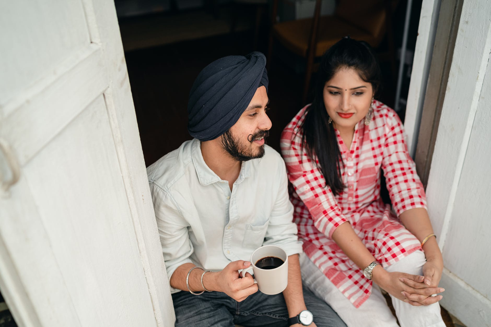 young married couple communicating on threshold of house