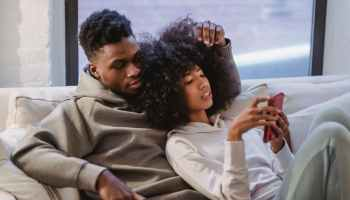 young black woman resting together with boyfriend and using smartphone