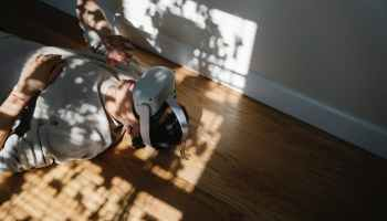 man exploring virtual reality in headset while resting on parquet