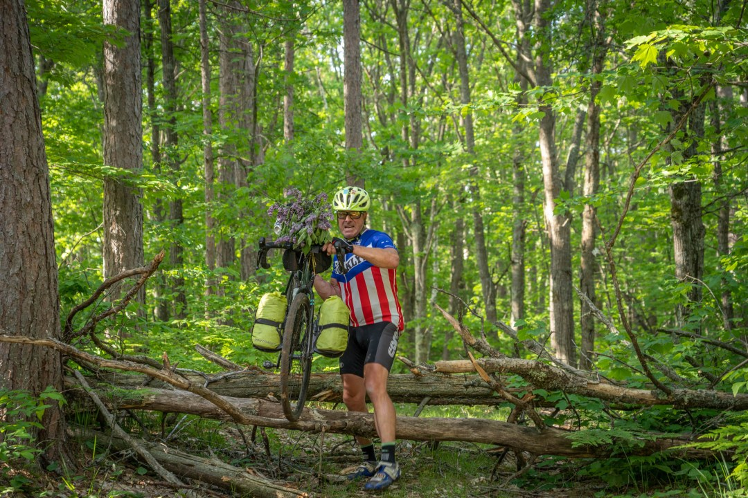 Man in Brooklun jersey carries bike over down tree in forest