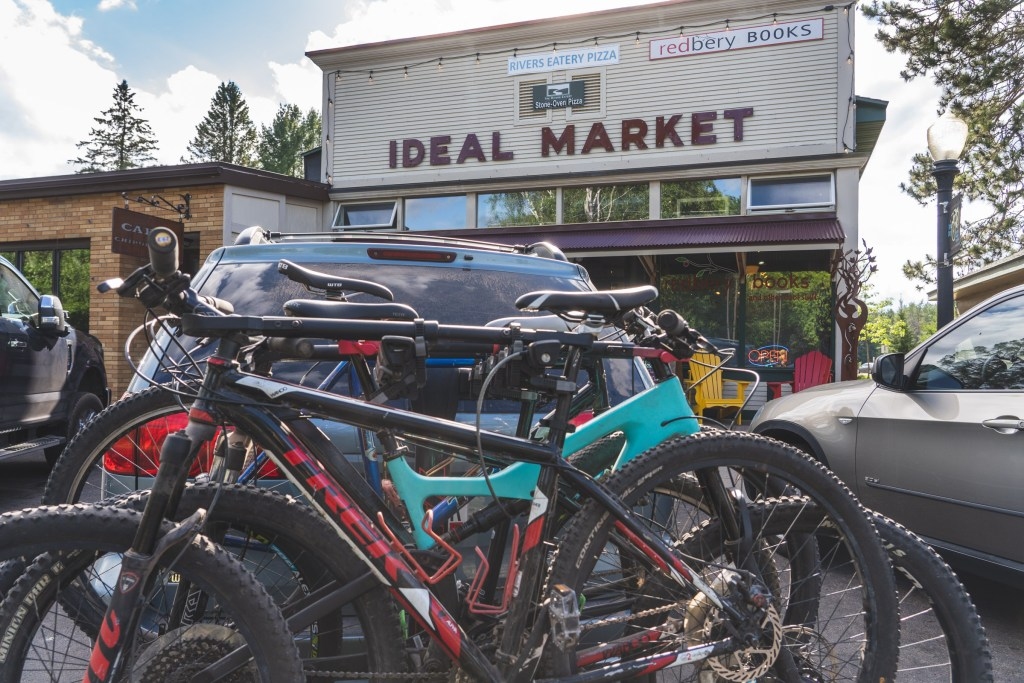 mountain bikes on a rear rack parked in front of The Ideal market in Cable