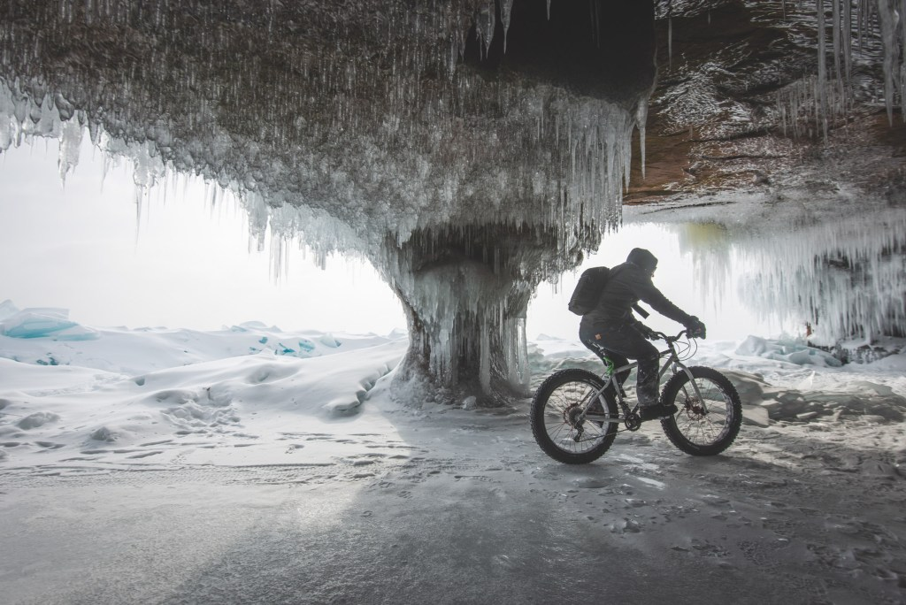 riding fat bike in frozen sea cave on Lake Superior