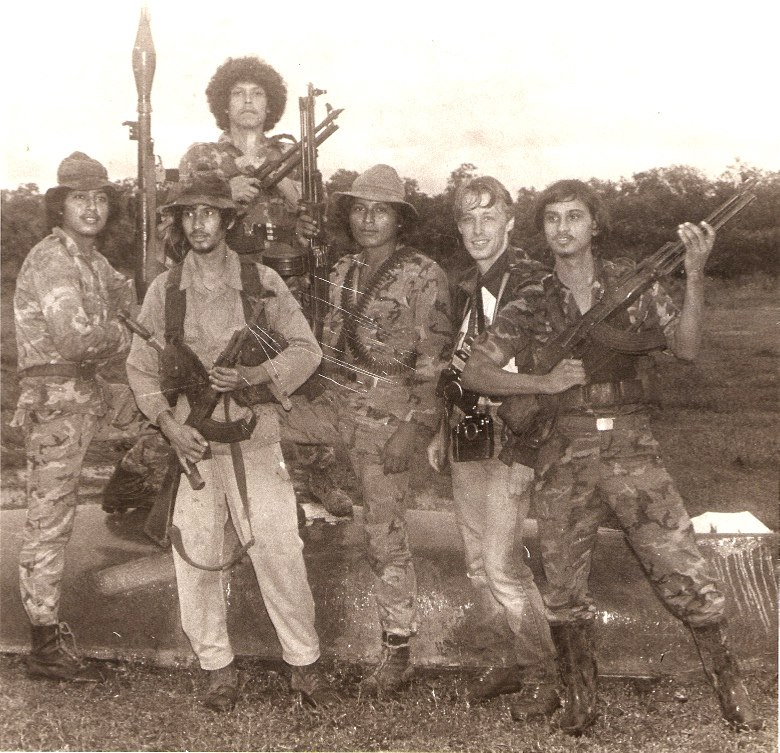 B&W photo of a photographer with camera who stands next to Sandinista soldiers.