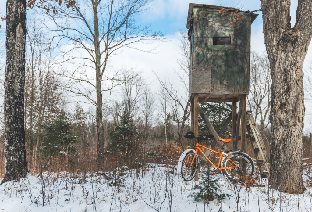 Orange fat bike leans against an elevated wood deer stand in the woods.