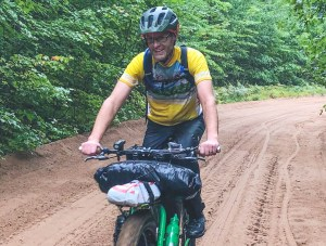 man smiles riding a bike in the rain on a sandy road