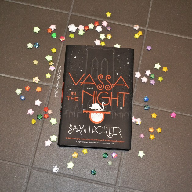 Vassa in the Night by Sarah Porter lying on the tiles surrounded by paper stars