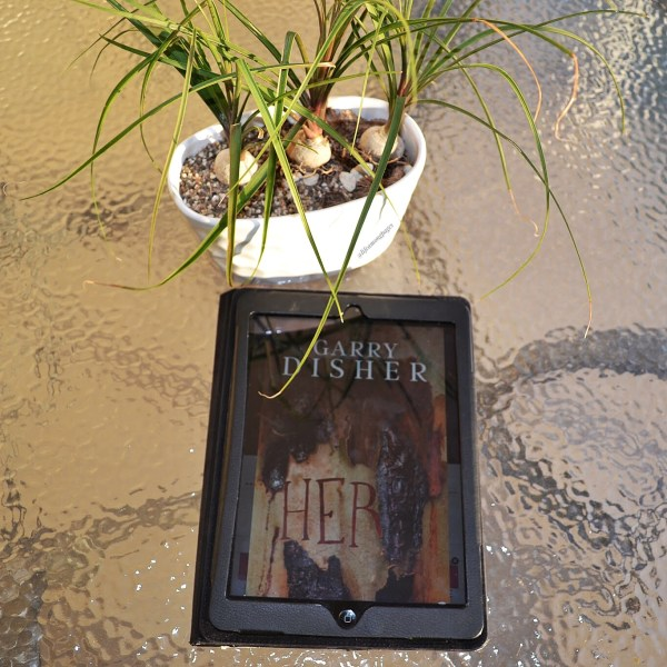 Cover of Her by Garry Dishner on a glass table with a potted chive plant