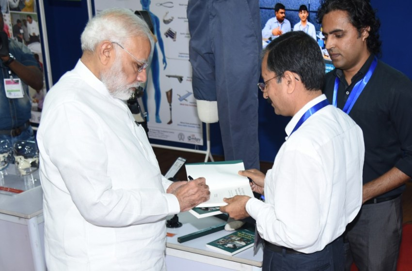 PM Modi autographs medical device innovation book