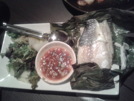 Baked fillet of sea bass with lemon grass and black pepper wrapped with banana leaf