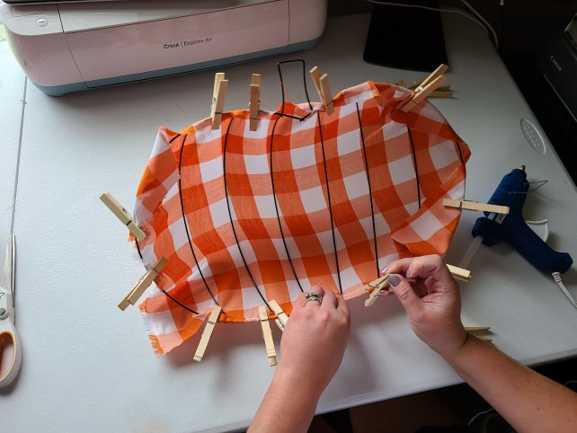 Using clothes pins to attach fabric to the Dollar Tree pumpkin wreath form.