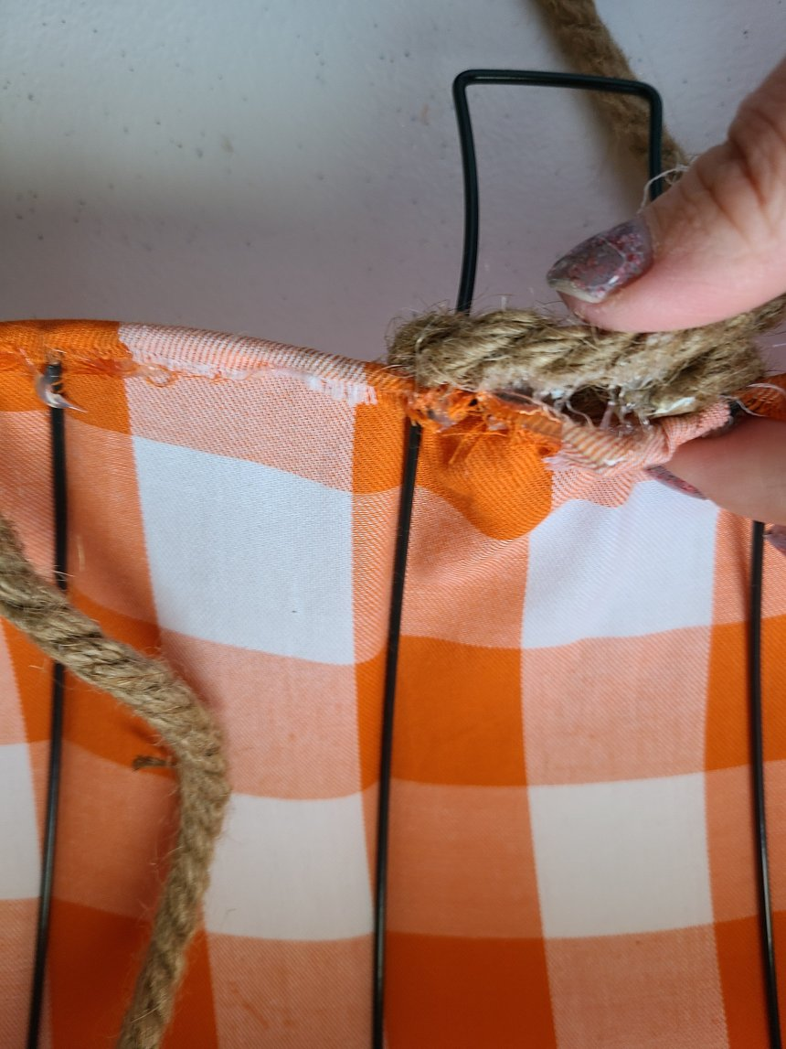 Wrapping nautical rope around the wire stem on the Dollar Tree pumpkin wreath form.