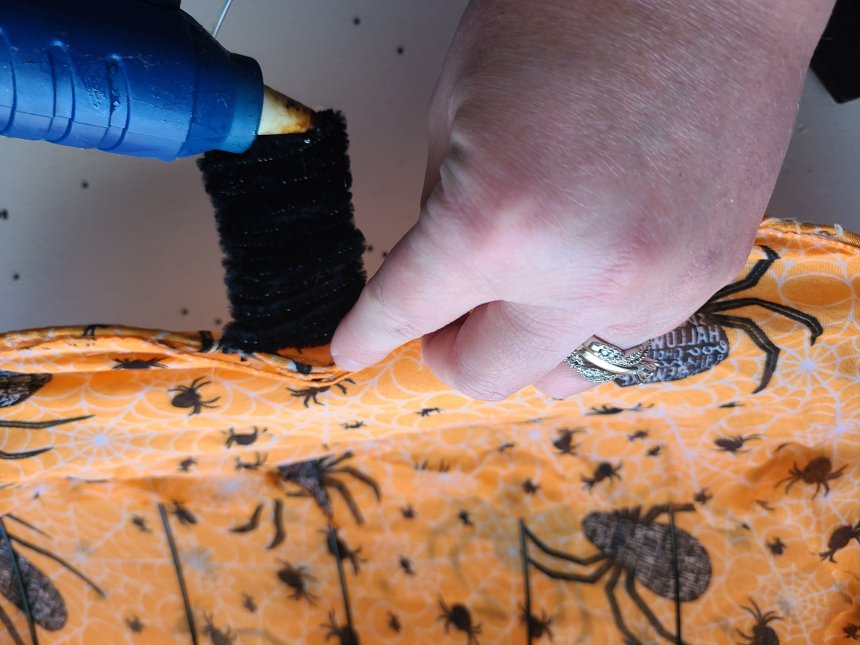 """Gluing the pipe cleaner across the top wire of the """"stem"""" of the Halloween pumpkin wreath."""