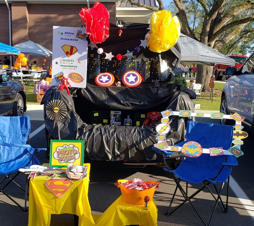 """Superhero trunk or treat idea. Full trunk decked out in tons of superhero decor. Action figures, Captain America """"shields,"""" paper flowers & fans, cityscape, photo booth & more."""