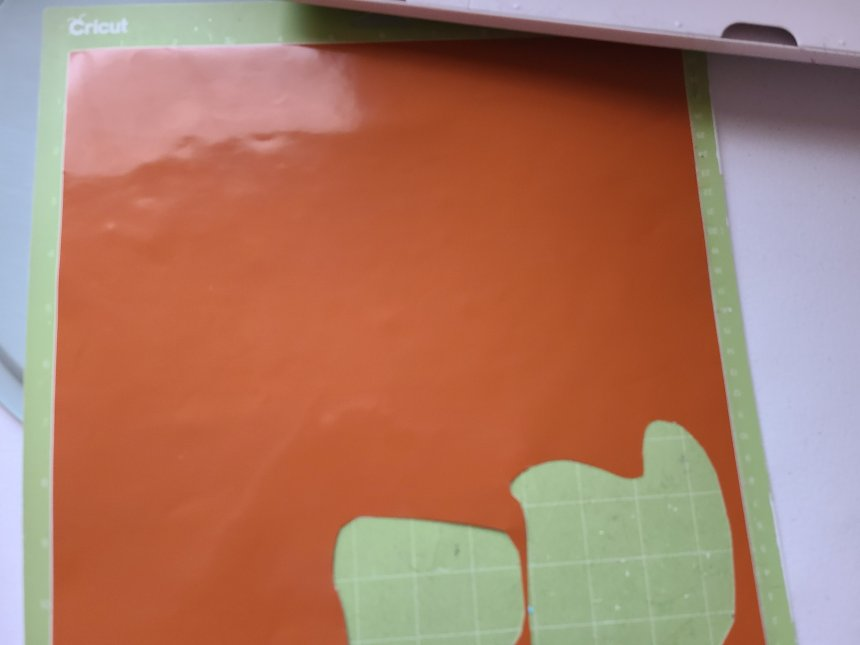 Orange vinyl placed on green standard grip Cricut cutting mat. This is the vinyl that will be used on the fall pizza pan wreath and the fall sign.
