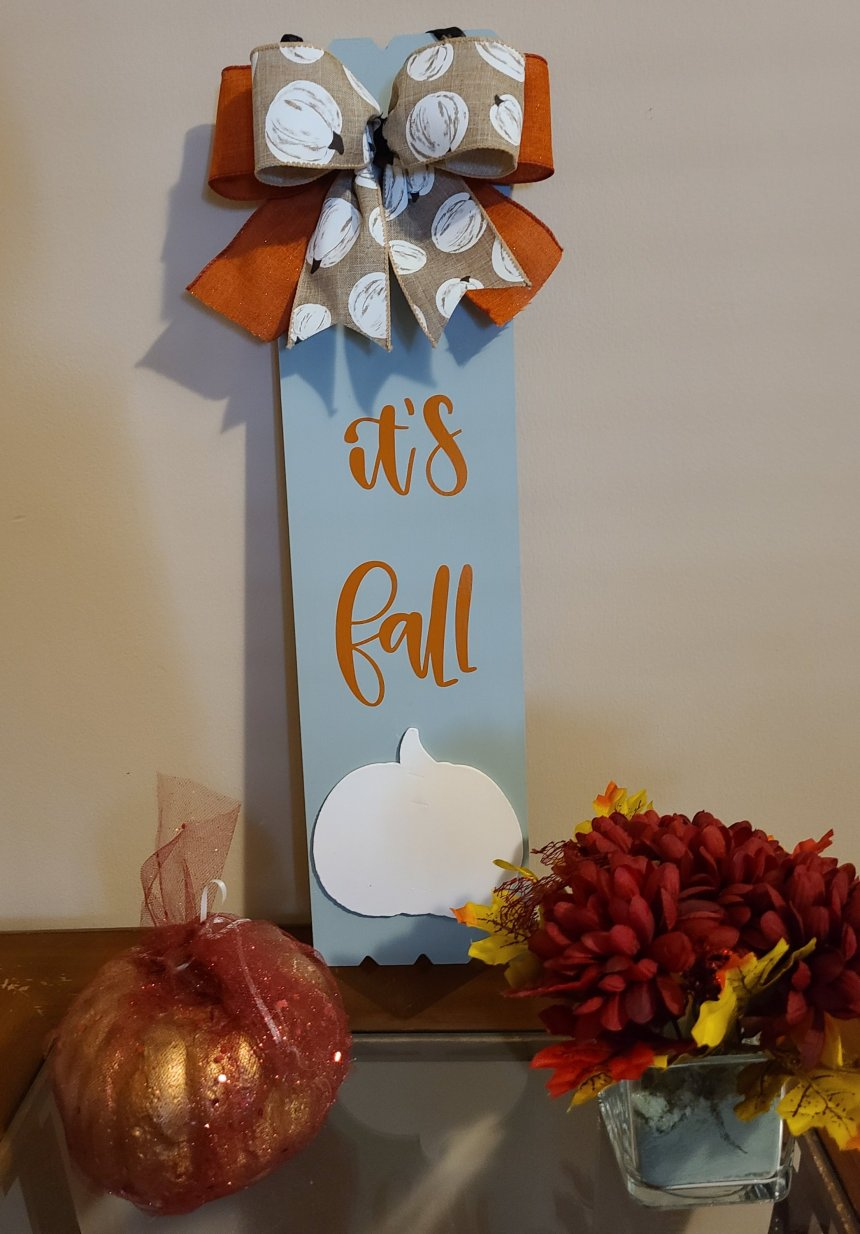 """Sage colored sign saying """"it's fall"""" with a white wood pumpkin at the bottom and a double bow at the top. This matches the fall pizza pan wreath."""
