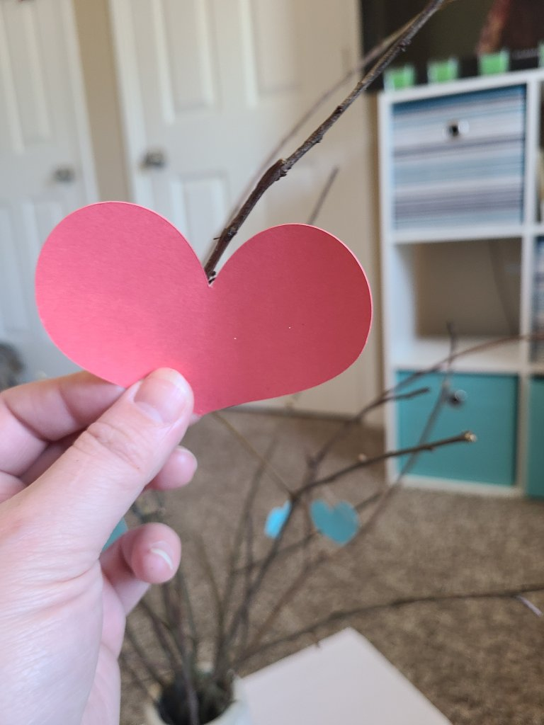 Put heart onto a stick in the Valentine's tree.