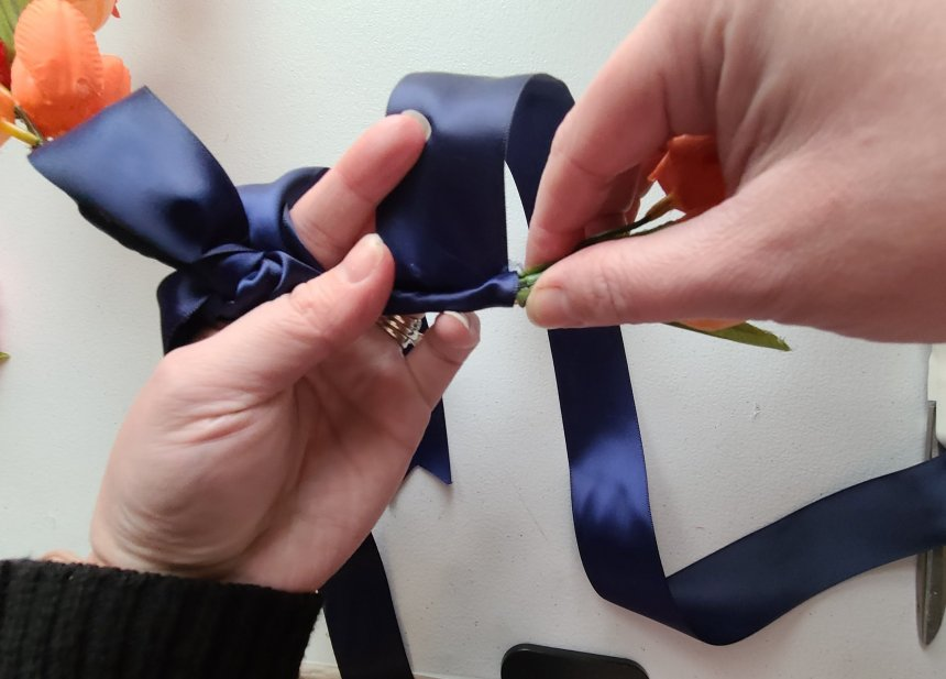 Wrap navy satin ribbon around the spring hoop wreath from the bottom of the tulip stems from the left of the bottom stems to the right side of the spring hoop wreath.