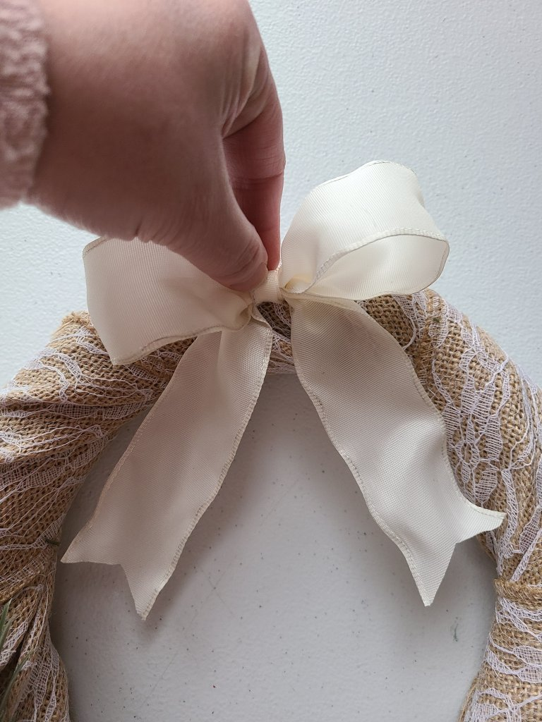Showing the bow glued on to the burlap at the top of the spring wreath.