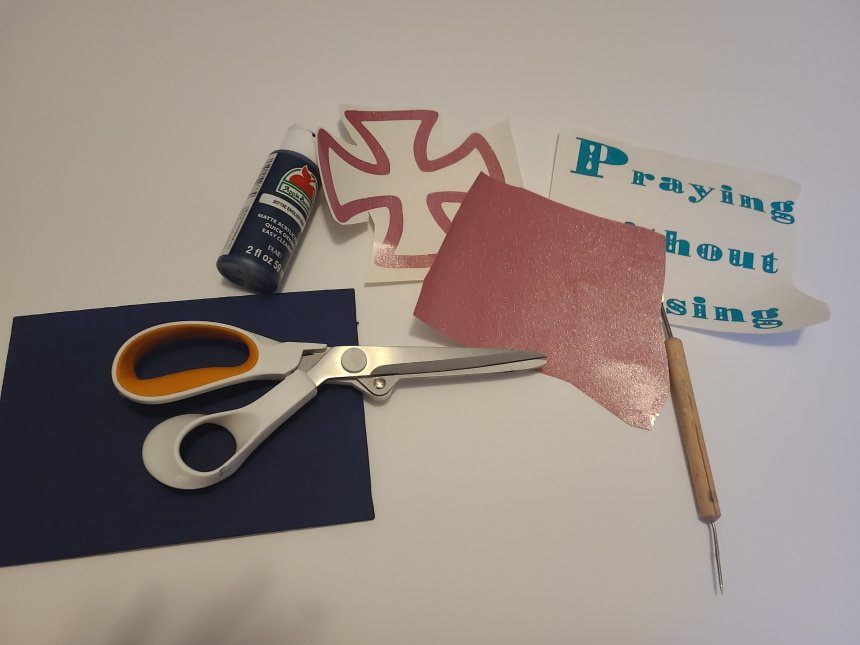 Supplies needed for prayer in progress sign. Scissors, 5x7 canvas, English navy acrylic paint, pink and teal vinyl, and a weeding tool.