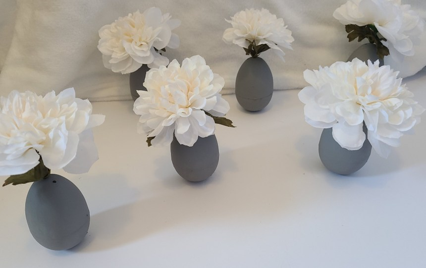 Set of 6 Easter egg vases with white flowers and gray painted eggs.
