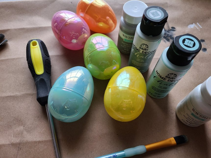 Supplies needed to make Easter egg vases. Six large plastic eggs, chalk paint, and a screwdriver.