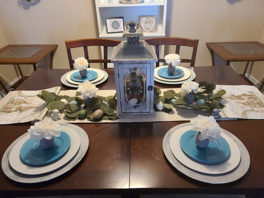 Four place settings on gray chargers holding white & turquoise plates and Easter egg vases on top. The center of the Easter tablescape holds a tan table runner with bunnies, greenery and egg vases.