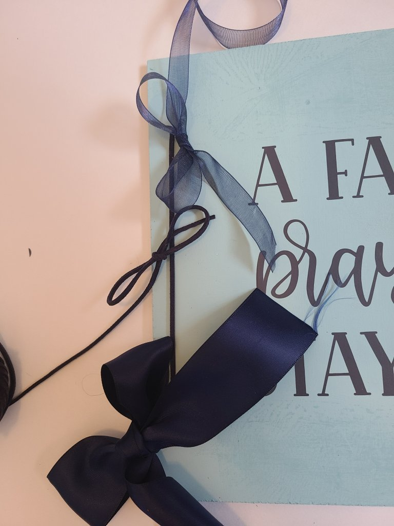 three navy bows with different ribbon types to put on the Dollar Tree Cricut sign