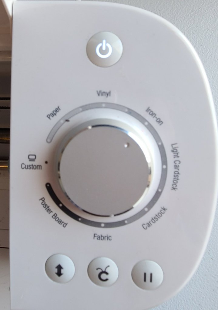 """Cricut die-cutting machine showing the dial and buttons on the right side of it. Dial is set to """"Iron-on."""""""