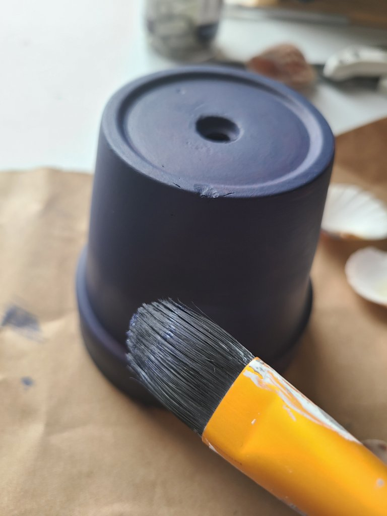 Painting a terracotta pot navy to become a nautical candleholder.