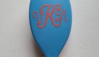 Vinyl monogram applied to a blue hairbrush.