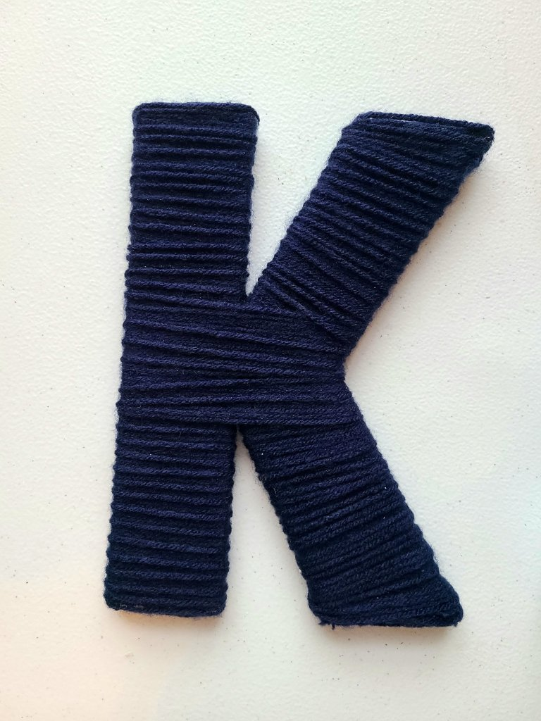 Nautical initial fully wrapped in navy yarn.