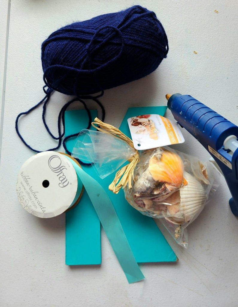 supplies needed to make a nautical initial- letter, seashells, satin ribbon, navy yarn, hot glue gun