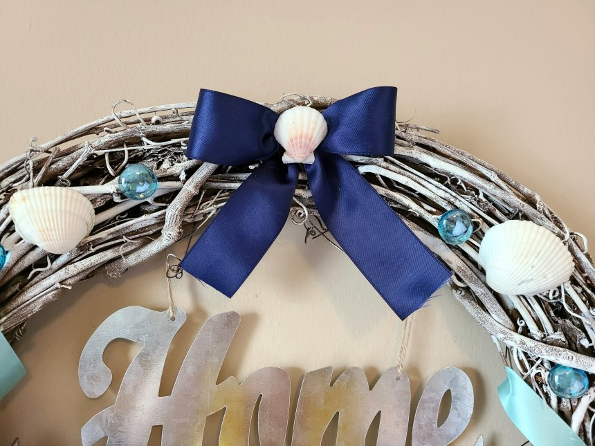 Navy satin ribbon glued to the top of the nautical beach wreath.