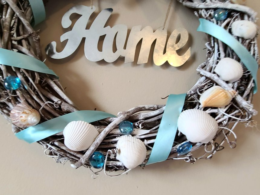 Picture of the bottom half of the beach wreath. Grapevine wreath painted white, with satin ribbon, blue gems, & white seashells.