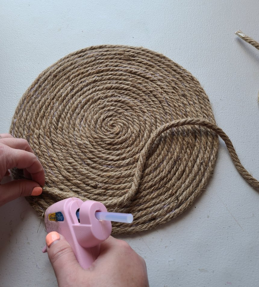 Putting hot glue on the outer ring of the placemat to start building the rope tray.