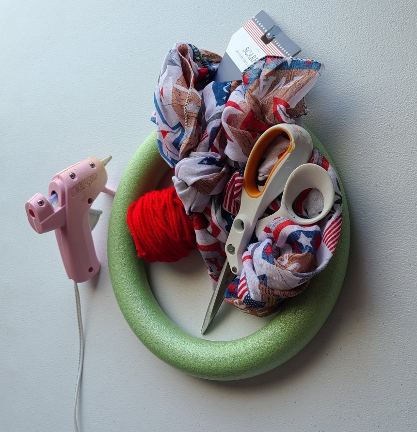 Supplies needed to make a scarf and yarn patriotic wreath, shown: hot glue gun, scissors, green styrofoam wreath form, red yarn, and red, white, and blue patterned scarf.