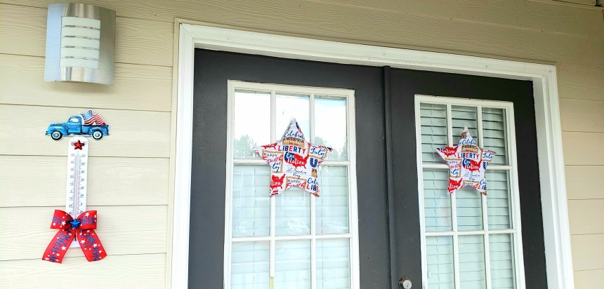 Shot of red white and blue outdoor decoration and two patriotic star wreaths hanging on the balcony.