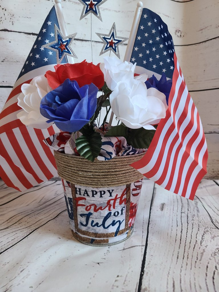 Patriotic centerpiece from a metal flower pot covered with red, white, and blue USA sayings and pictures, two American flags, roses in red, white, and blue, and a silver stars.