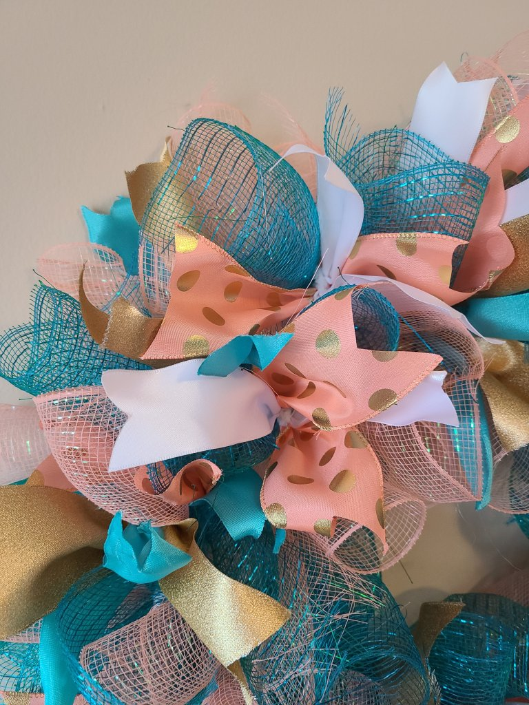 Section of wreath with ribbon added into pipe cleaners with deco mesh spirals.