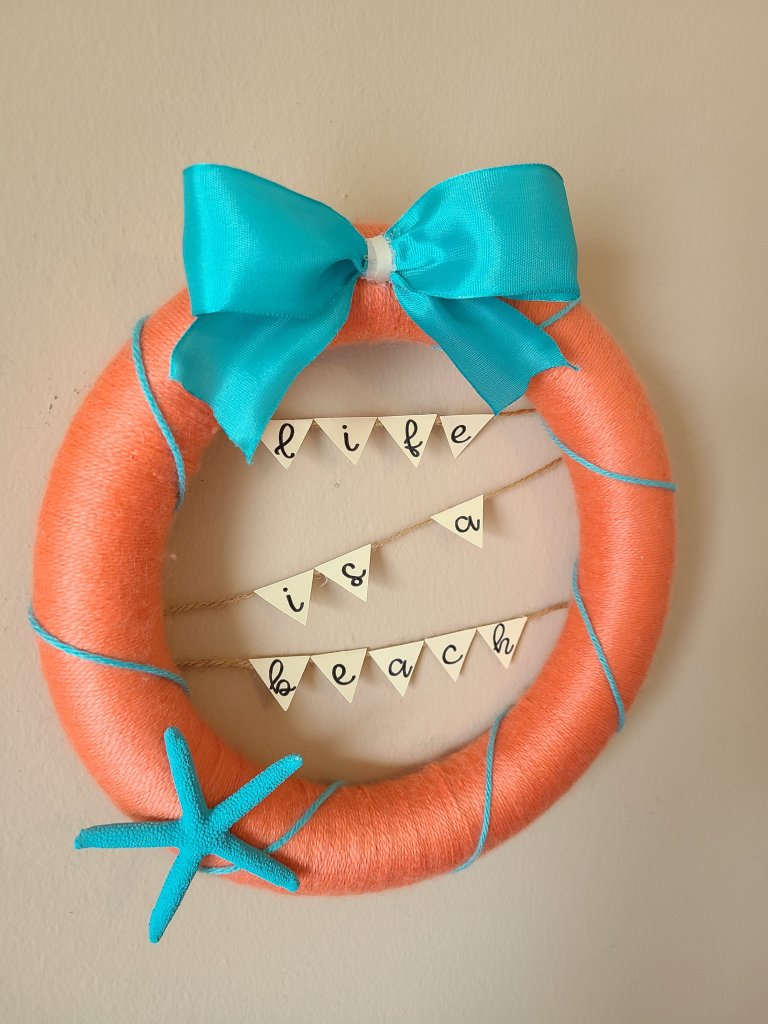 Beachy melon colored yarn wreath with teal bow and a banner with a Cricut in the center.