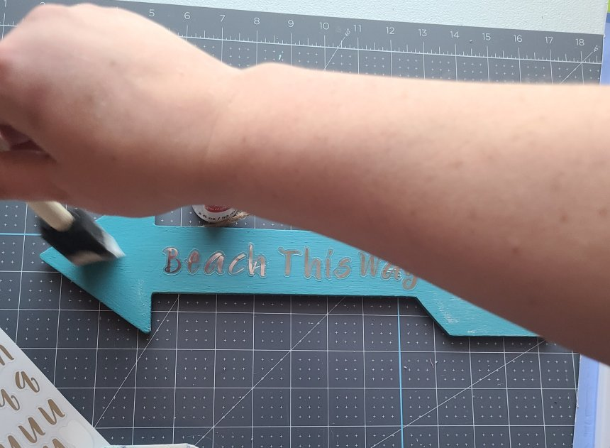 white paint being added to Teal painted wood arrow for porch decor