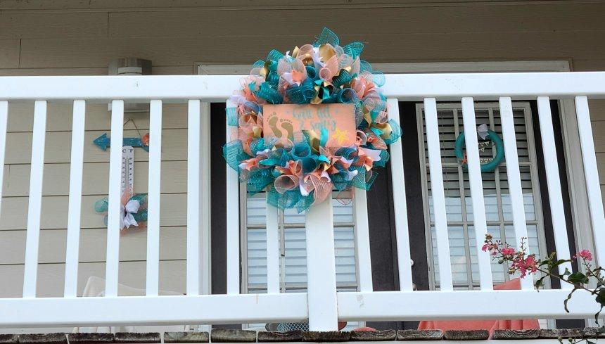 Spiral Deco Mesh wreath as porch decor attached to white balcony railing.