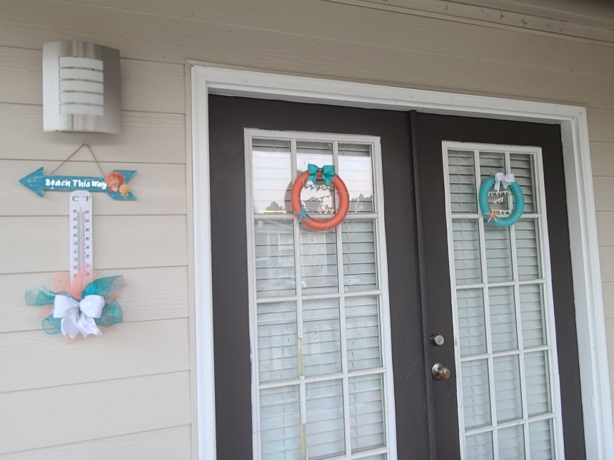 Porch decor- coral yarn wreath & turquoise yarn wreath on two French doors & beach sign & bow on outdoor thermometer.