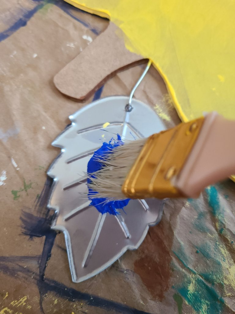 Leaf on the teacher door hanger being painted royal blue using a paint brush.