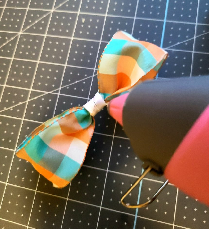 Adding hot glue to the center of the fall bow that will be added to the reversible faux books.