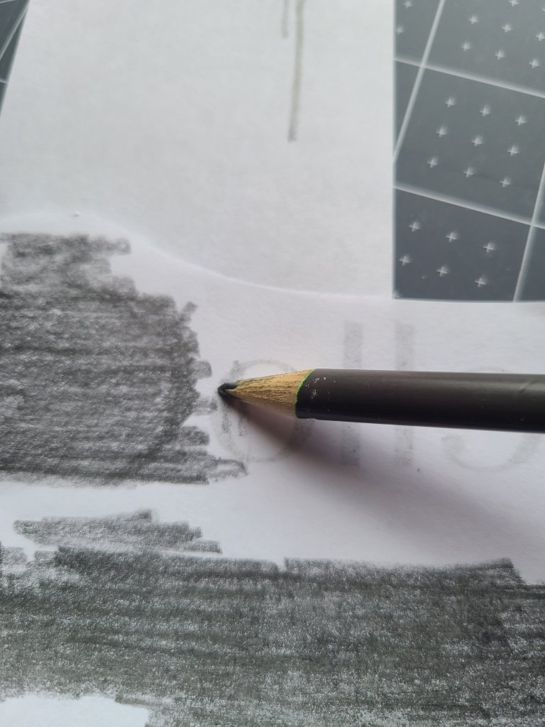 Pencil being used to cover the back of the design so that it can be transferred onto the DIY sign,