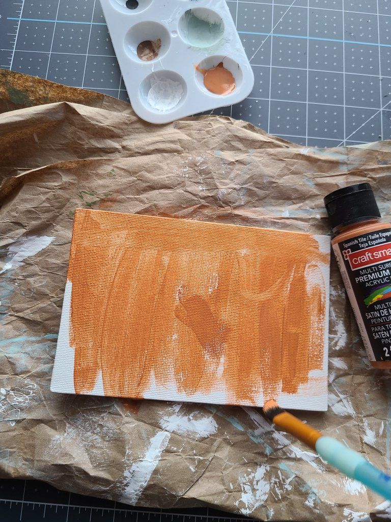 The canvas that will be the sign on the DIY fall centerpiece is being painted burnt sienna.